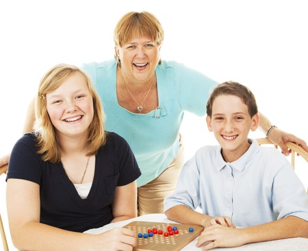 Mom and two kids have fun playing board games.  Isolated on white.   photo