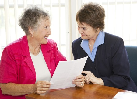 senior reading: Senior and middle-aged businesswomen discussing a contract. Stock Photo