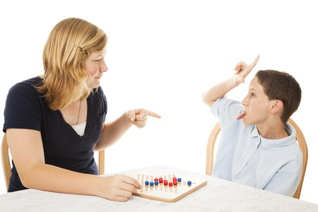obnoxious: Little brother driving his teenage sister crazy while they play a board game.  Isolated on white. Stock Photo
