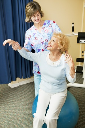 Physical therapist helps senior woman workout on a pilates ball.   Stockfoto