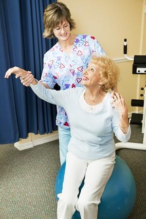 Physical therapist helps senior woman workout on a pilates ball.   Фото со стока