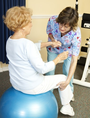 therapists: Senior woman on yoga ball, working with a physical therapist.