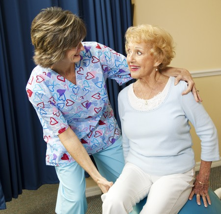 physical: Physical therapist helps a senior woman exercise using a pilates ball.