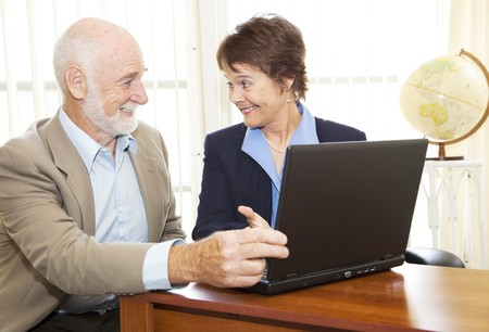 Mature businesswoman giving financial advice to senior man. Stock Photo - 7033994