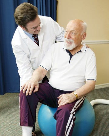 Chiropractor does physical therapy with a senior man, using a pilates ball.