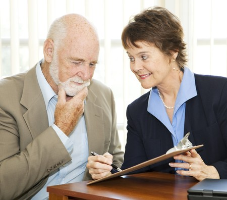 reluctant: Senior man reading and thinking about a contract while eager businesswoman encourages him to sign.   Stock Photo