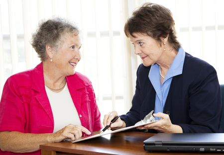 Mature businesswoman discusses a contract with her senior client.  Could also be sales related.