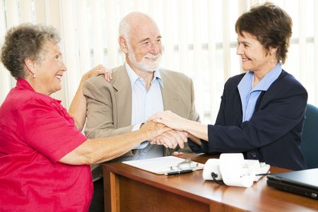 shakes hands: Senior couple shakes hands with their financial advisor or broker.   Stock Photo