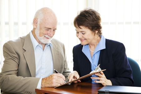 Senior man signing a contract while his broker looks on.   photo