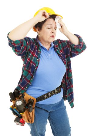 tired: Tired female construction worker wipes sweat from her forehead.