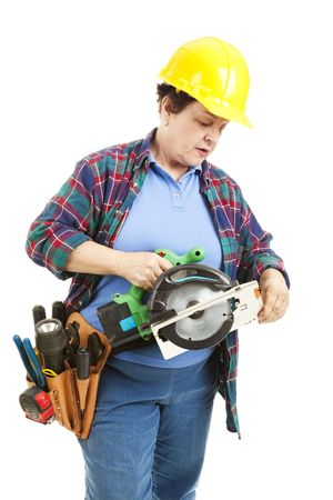 inexperienced: Female contruction worker trying to figure out how to use a circular saw.