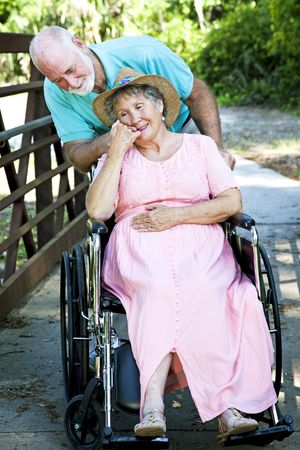 Senior man caring for his disabled wife in wheelchair. photo