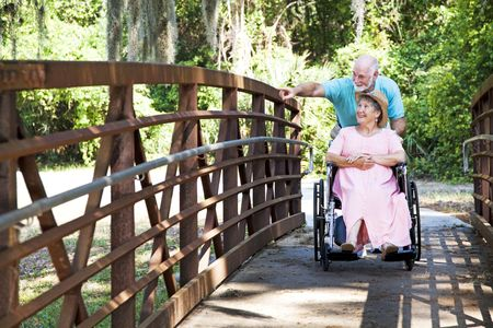 pushes: Senior man pushes his disabled wifes wheelchair through the park.