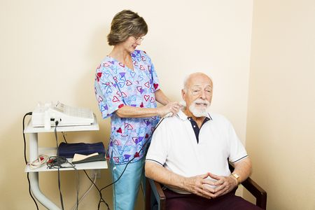 Chiropractic nurse gives ultrasound therapy to a senior patient for relief of neck pain.   photo