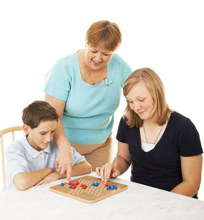 Mother and her two children playing a board game together.  White background.   photo