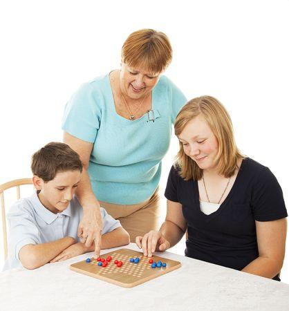 brettspiel: Mutter und ihre zwei Kinder, die ein Board-Spiel zusammen spielen.  Wei�er Hintergrund.