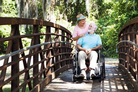 personas discapacitadas: Senior esposa toma a su marido discapacitado en un paseo por el parque.   Foto de archivo