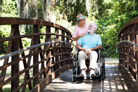 Senior wife takes her disabled husband on a walk through the park.