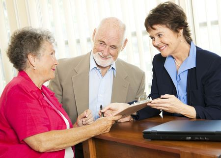 Senior couple working with a broker or advisor, signing paperwork.
