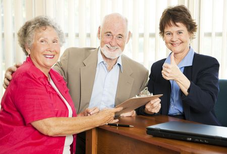 Financial consultant gives thumbs up as she advises retired couple.   photo