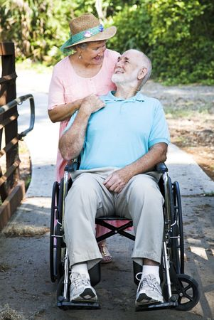 taking a wife: Disabled senior man in wheelchair with his loving wife taking care of him.