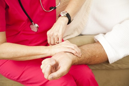 Closeup of a home health nurses hands taking an elderly patients pulse.   photo