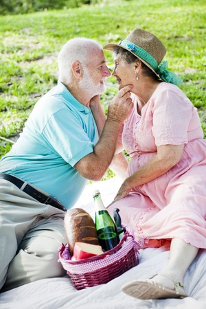 Senior couple on a picnic gets romatic.   photo
