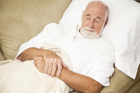 agotado: Sonido de Senior hombre dormido en el sof�, sufriendo de un resfriado.   Foto de archivo