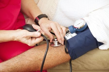 home health care: Nurse taking a patients blood pressure using a sphygmomanometer.  Closeup view.   Stock Photo