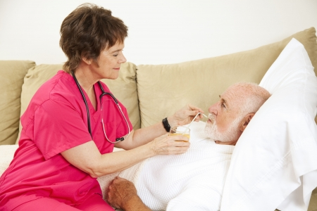 home care nurse: Home nurse helps elderly patient drink a glass of orange juice.