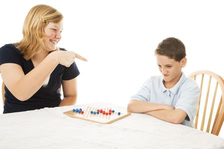 Teen girl makes fun of her little brother during a board game.  White background.