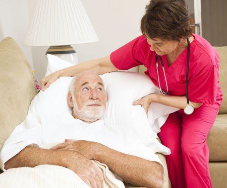 sick person: Enfermera de salud en el hogar fluffs almohada de un paciente anciano.