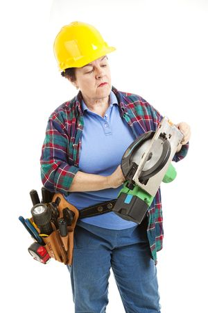 Female worker gets ready to fix a circular saw.   photo