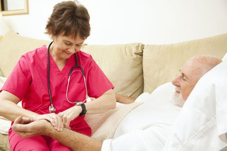 Home health nurse taking the pulse of an elderly, home-bound patient.   Stock Photo
