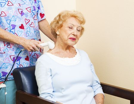 Senior chiropractic patient gets ultrasound therapy for her neck pain.   photo