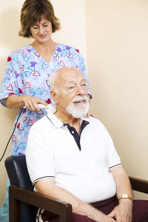 Senior chiropractic patient gets relief from neck pain through ultrasound technology.   photo