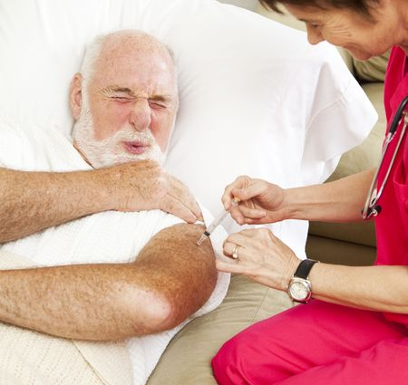 Senior man gets a painful injection from a home health nurse.   photo