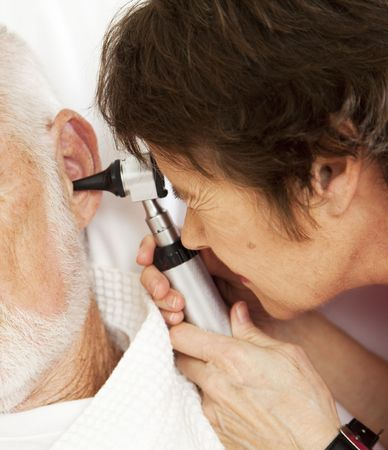 otoscope: Closeup of nurse or doctor looking in a patients ears with an otoscope.