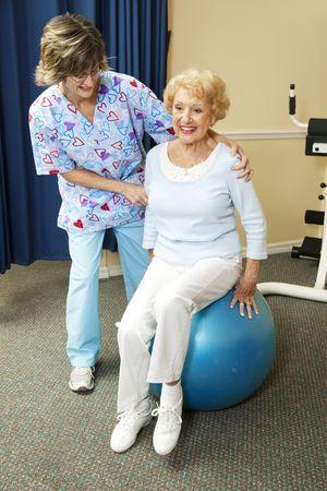 Fysieke therapeut helpt een senior vrouw uitoefenen op een pilates bal.  Stockfoto
