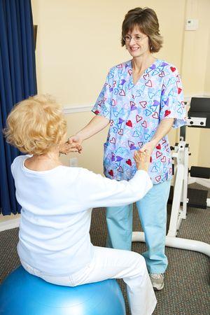 年配の女性、物理療法士の助けを借りて練習。