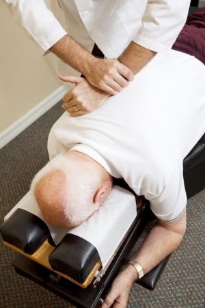 osteopath: Closeup of chiropractors hands adjusting a senior mans spine.