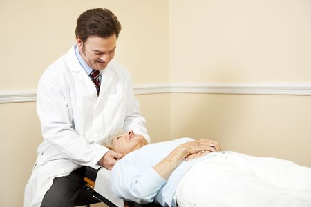 Chiropractor adjusting the neck of an elderly female patient.   photo