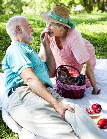 Romantic senior couple on a picnic.  Hes feeding her grapes. Stock Photo