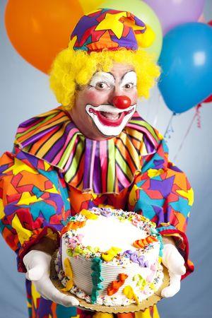 payaso: Feliz cumplea�os payaso sosteniendo un pastel de cumplea�os. Pastel est� listo para el texto.  Foto de archivo