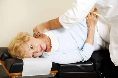 Senior woman getting an adjustment from her chiropractor.