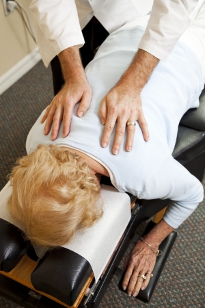 manipulation: Closeup of a chiropractors hands as he adjusts a senior patien in his office.