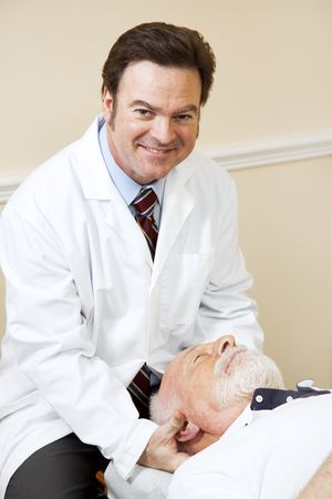 Handsome, smiling chiropractor adjusting a senior mans neck.   photo
