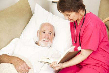 Friendly home caregiver reads to an elderly patient.   photo