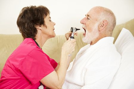 depressor: Home health care nurse uses an otoscope and tongue depressor to look in a patients mouth.   Stock Photo