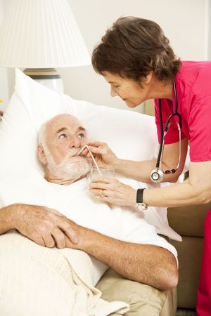 home health care: Friendly home health nurse gives juice to an elderly patient.